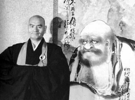 Maitre Taisen Deshimaru Roshi, devant une calligraphie représentant Boddhidharma